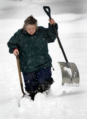 "Barbara Oster, uses two shovels to help her walk through the thick snow at her mother's home in Newtown after an overnight snowfall, Friday, March 8, 2013. ""I wasn't prepared,"" says, Oster, of the deeper-than-expected snow. Photo: Carol Kaliff / The News-Times"