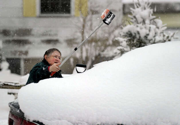 Barbara Oster reaches to clear the snow off of her car Friday, March 8, 2013. Oster, of Brookfield, was visiting her mother in Newtown. Photo: Carol Kaliff / The News-Times