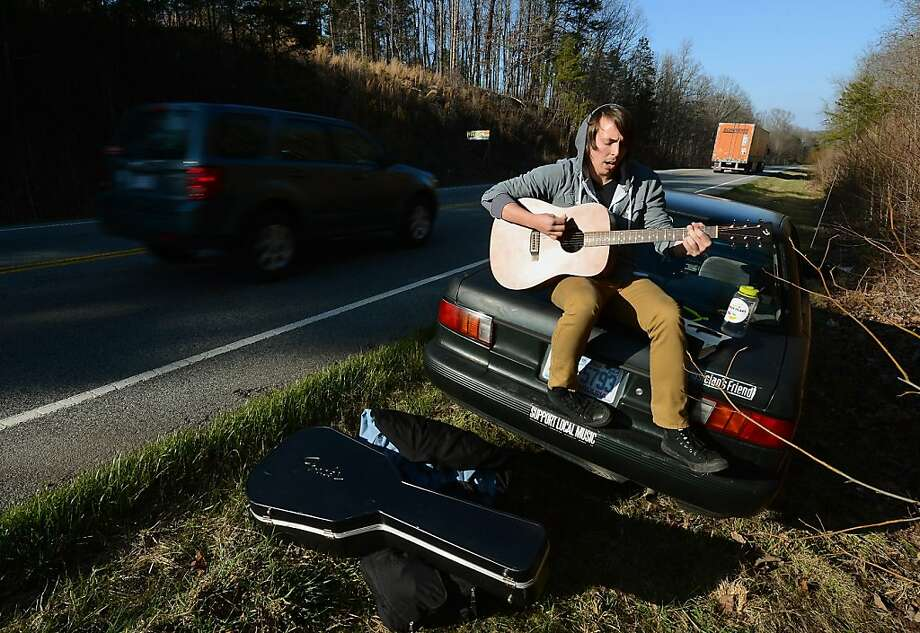 'I've got those no-roadside-assistance blues …': Pfeifer University junior Zach Thompson passes the time by playing a song along Route 49 North outside of Mount Pleasant, N.C. He was waiting for a family member to pick him up after his car broke down. Photo: Jeff Siner, Associated Press