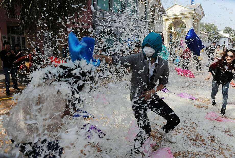 This picture taken on March 7, 2013 shows people on a pillow fight game to celebrate the coming International Women's Day in Changsha, southwest China's Hunan province. The organizers said they would like to ease the stress in daily life of both female and male citizens. Photo: Str, AFP/Getty Images
