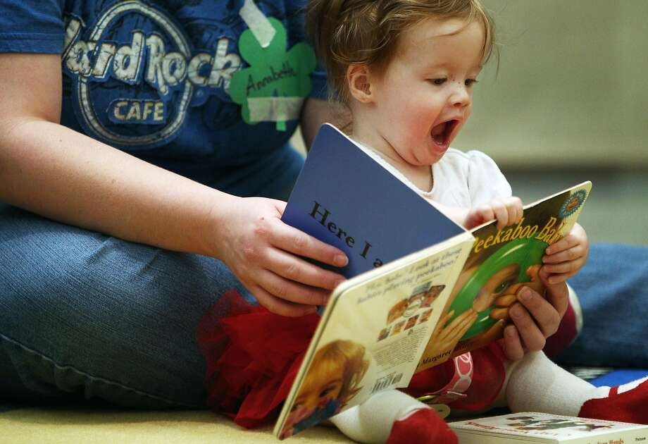 "Despite the limited character development and predictable plot, 8-month-old Annabeth Geminm is nonetheless  enthralled by the story of ""Peekaboo Baby,"" read by her mom, Anna, at a library in Collierville, Tenn. Photo: Mike Brown, Associated Press"