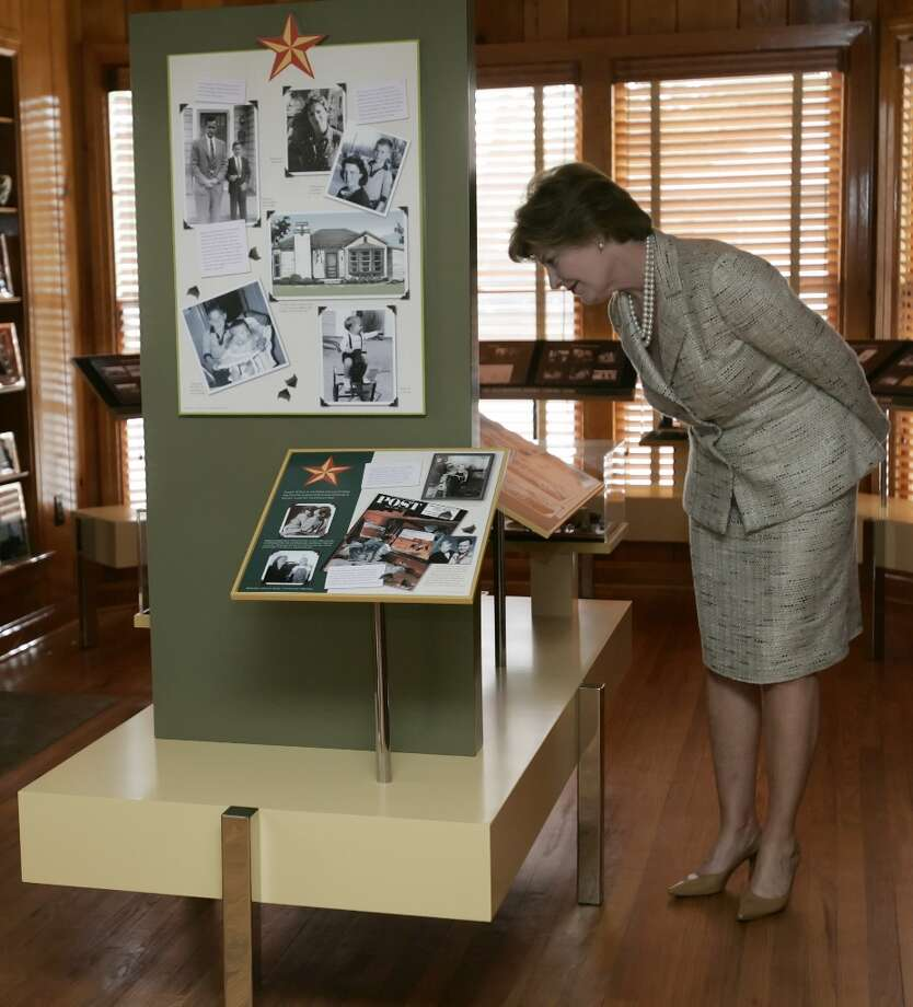 First lady Laura Bush looks at an informational exhibit at the restored childhood home of U.S. President George W. Bush's in Midland, Texas, April 10, 2006. The first lady and former U.S. President George H. W. Bush and Barbara Bush will officially dedicate the facility April 11. Bush lived in the house from 1952-1955.   REUTERS/Tony Gutierrez/Pool Photo: POOL, REUTERS / X80003