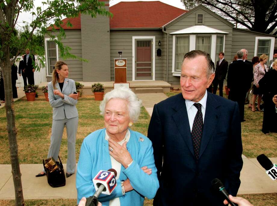 Former President George H.W. Bush, right, and Barbara Bush, left, respond to questions as they stand in front of the childhood home of George W. Bush in Midland, Texas, Tuesday, April 11, 2006. The Bushes were on hand for the official dedication of the home Tuesday. Photo: TONY GUTIERREZ, AP / AP