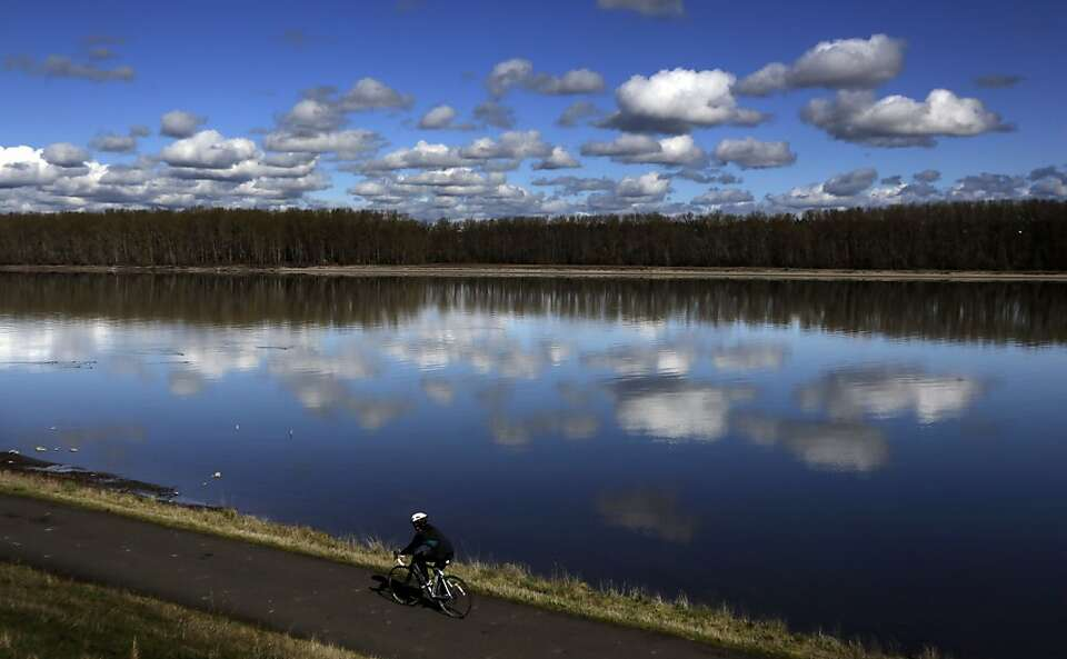 Puffy pedal: A bicyclist glides past a glassy stretch of the Columbia River in Portland, Ore.