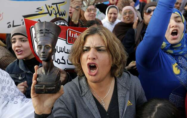 An Egyptian woman raises a statue of pharaonic Queen Hatshepsut, the only woman that ruled Egypt, as she shouts slogans during a demonstration in Cairo, Egypt, Friday, March 8, 2013, marking the International Women's Day. Photo: Amr Nabil, Associated Press