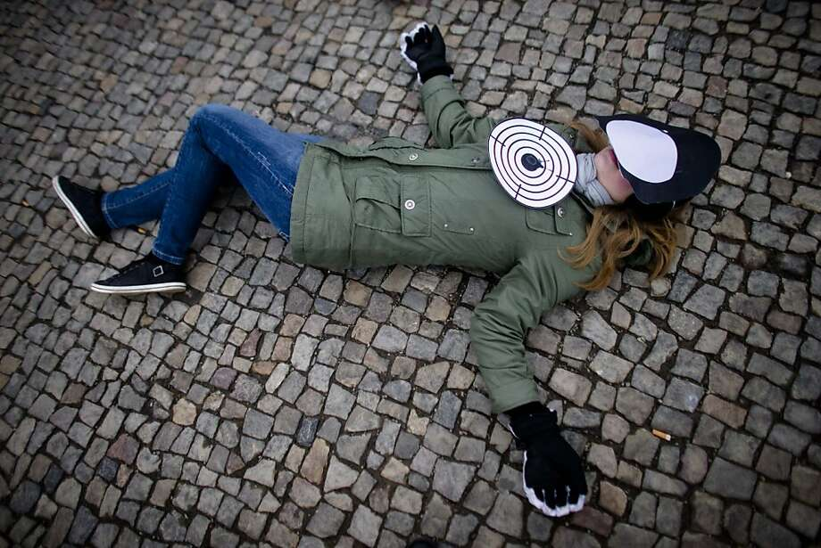 A female activist of the human rights organization Amnesty International with a target and a faceless mask lays on the ground during a demonstration marking the International Women's Day at the Paiser Platz in Berlin, Germany, Friday, March 8, 2013. Photo: Markus Schreiber, Associated Press
