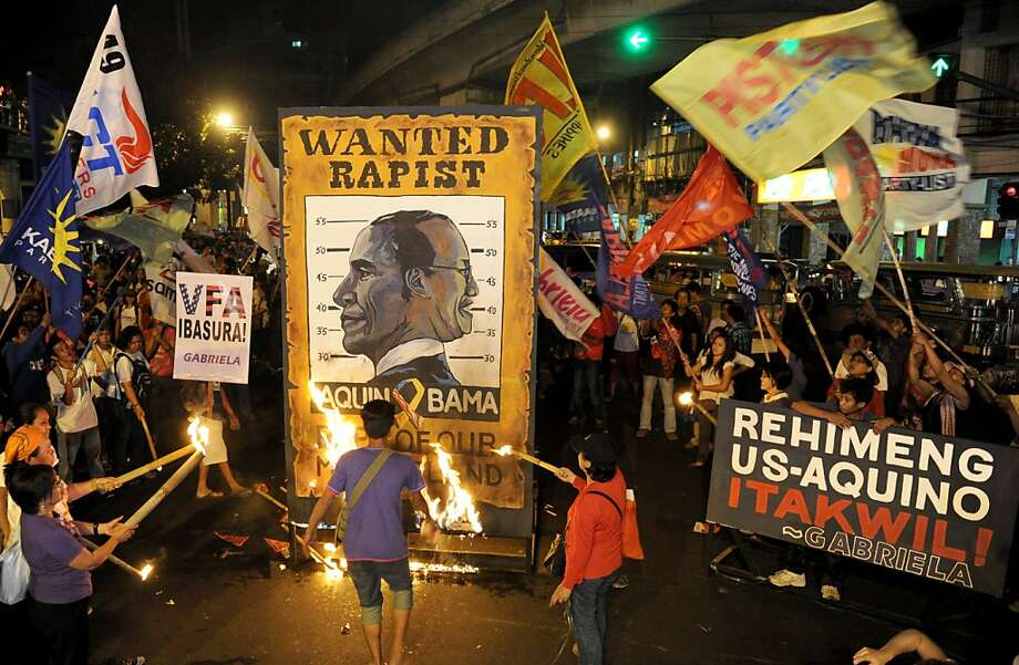 Protesters burn a poster bearing a joint caricature of US President Obama (left) and Philippine President Aquino (right) as they march towards the Presidential Malacanang Palace to mark International Women's Day in Manila on March 8, 2013. The women's group called for gender equality, denounced the presence of the US military in the country, and blamed the Aquino government for surrendering to US policy. Photo: Jay Directo, AFP/Getty Images