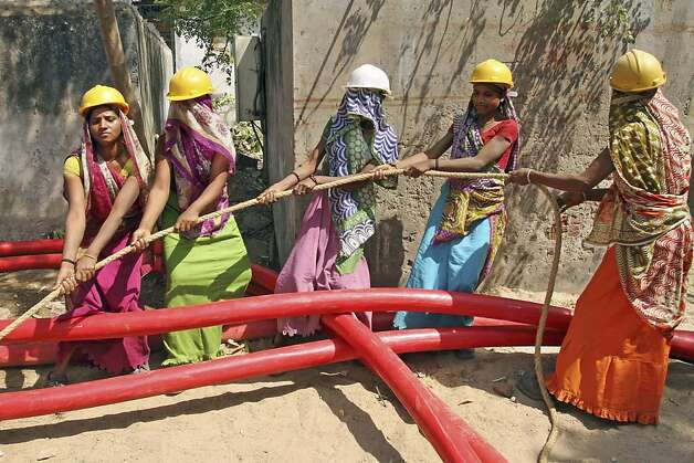 Indian women laborers work to lay a cable for an electricity company on International Women's Day in Ahmadabad, India, Friday, March 8, 2013. Photo: Ajit Solanki, Associated Press