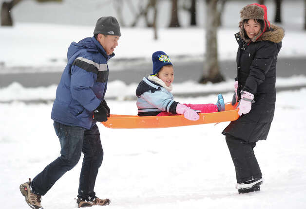 Aaliya Einsmann, 3, of Stamford, gets carried up a small hill on her sled by her grandparents Yuji, left, and Michun Yokobori, also of Stamford, while sledding at Bruce Park in Greenwich, Friday, March 8, 2013. Photo: Bob Luckey / Greenwich Time
