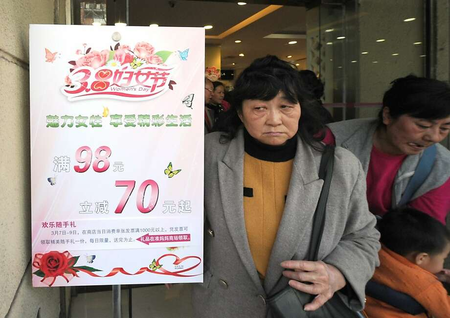 Women shop at a clothes store in Shanghai with discounts for International Women's Day on March 8, 2013. International Women's Day in China is celebrated with various events including discount shopping for women at malls in cities around China. Photo: Peter Parks, AFP/Getty Images
