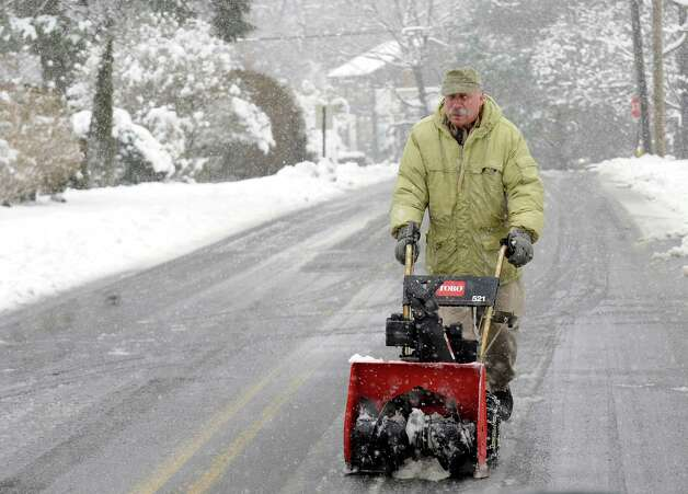 A man walks his snowblower up the middle of Maple St. in Milford, Conn. on Friday March 8, 2013. Photo: Cathy Zuraw / Connecticut Post