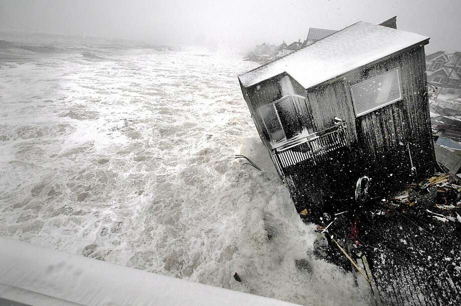 Goodbye, summer home:Churning surf driven by winds from a slow-moving nor'easter far out in the Atlantic surrounds a partially collapsed house on the Plum Island seacoast in Newbury, Mass. Photo: Jim Vaiknoras, Associated Press
