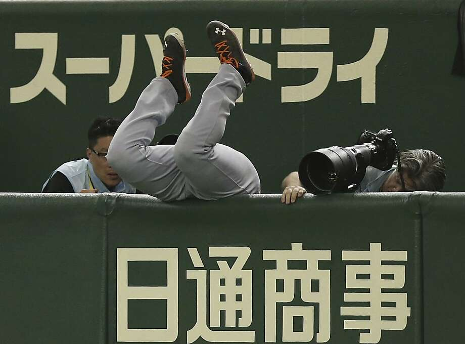 Take a bow, Curt! Netherlands' first baseman Curt Smith tumbles into the photographers' pit while snagging a foul ball during a World Baseball Classic game in Tokyo. Photo: Toru Takahashi, Associated Press