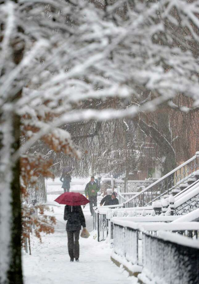A pedestrian shields herself from the elements as she walk on Elk Street during a snow storm  March 8, 2013, in Albany, N.Y.   (Skip Dickstein/Times Union) Photo: SKIP DICKSTEIN, ALBANY TIMES UNION