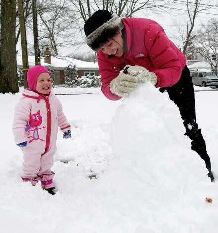 Willow Gray, 2, and her mother, Alissa, build a snowman outside their Stamford home on Friday, March 8, 2013. Photo: Lindsay Perry / Stamford Advocate