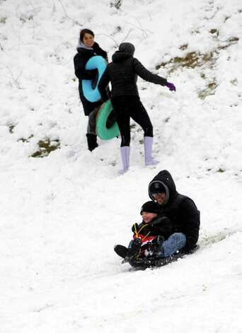 Sledders slide down a hill at Cummings Park in Stamford on Friday, March 8, 2013. Photo: Lindsay Perry / Stamford Advocate