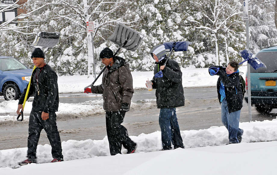 From left, Jahni Robinson, 19, Manny Holton, 20, Vincent Ward, 12, and Austin Ward, 11, all of Albany, walk near Washington Park looking for work with their shovels during a snow storm on Friday March 8, 2013 in Albany, N.Y. (Lori Van Buren / Times Union) Photo: Lori Van Buren