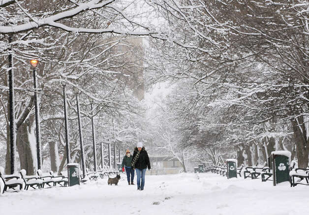 People walk in Washington Park during a snow storm on Friday March 8, 2013 in Albany, N.Y. (Lori Van Buren / Times Union) Photo: Lori Van Buren