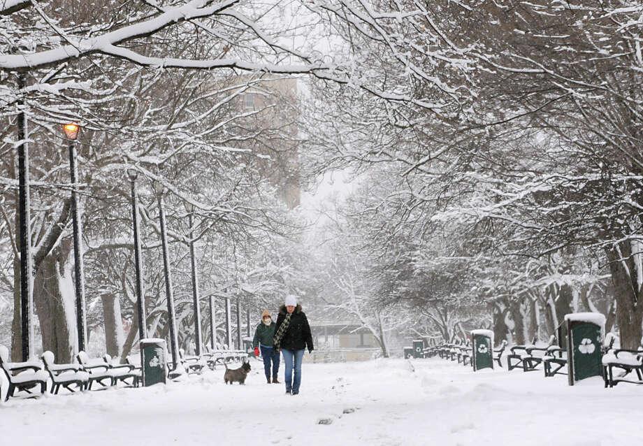 People walk in Washington Park during a snow storm on Friday March 8, 2013 in Albany, N.Y. (Lori Van Buren / Times Union) Photo: Lori Van Buren