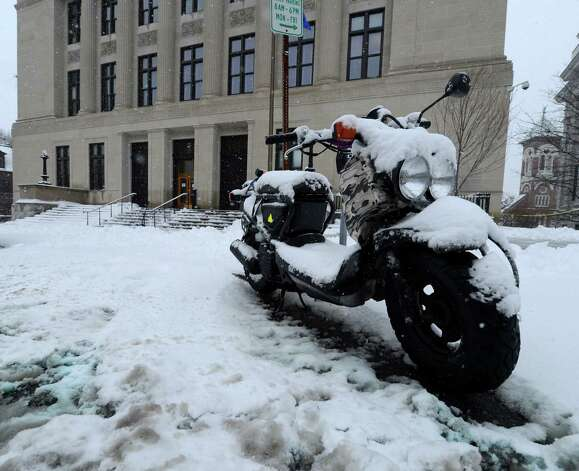 A motor bike sits idle and covered with snow in front of the Albany County Courthouse during a snow storm  March 8, 2013, in Albany, N.Y.   (Skip Dickstein/Times Union) Photo: SKIP DICKSTEIN