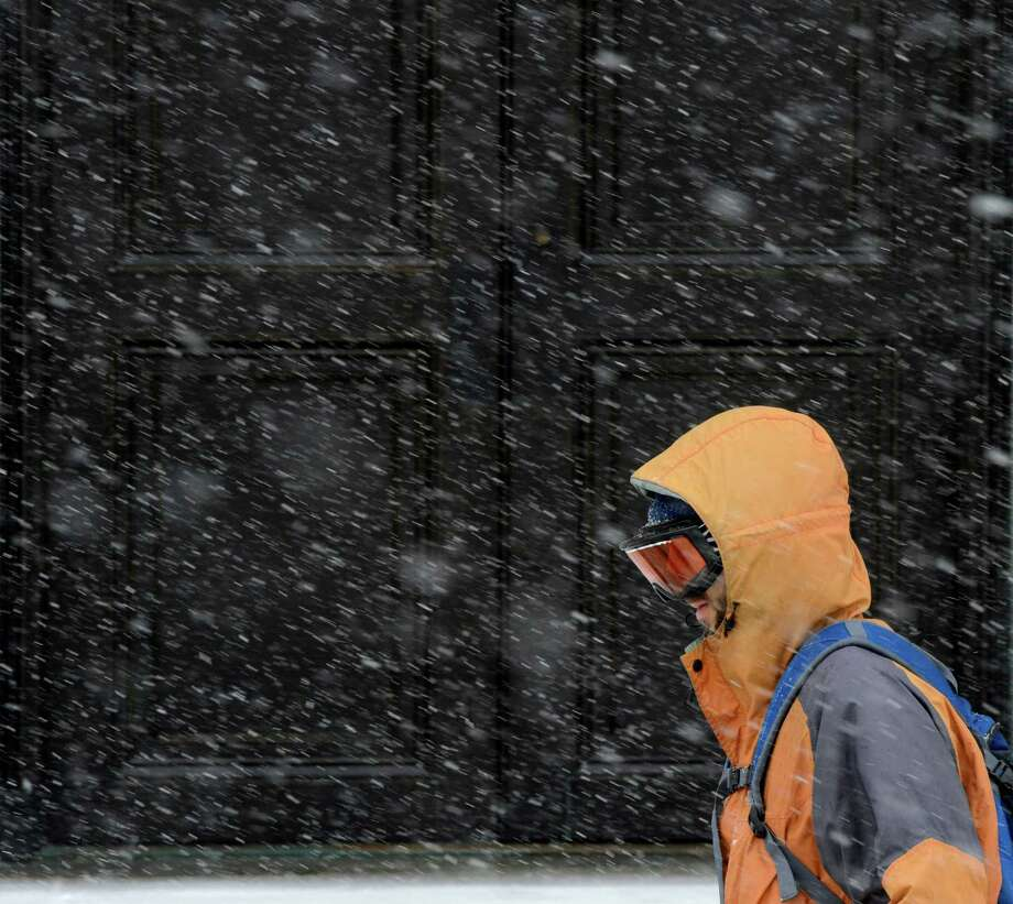An intrepid commuter walks in front of the Albany County Courthouse during a snow storm which has him protecting himself with ski goggles March 8, 2013, in Albany, N.Y.   (Skip Dickstein/Times Union) Photo: SKIP DICKSTEIN