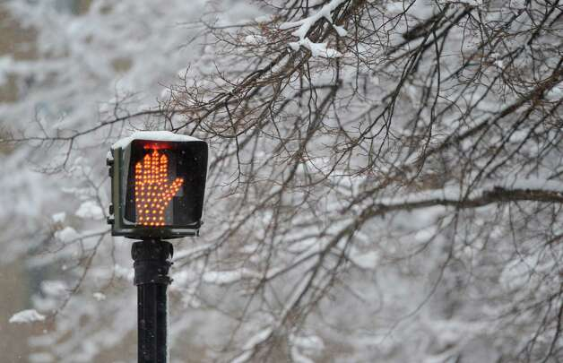A street crossing sign holds up the foot traffic on Elk Street during a snow storm  March 8, 2013, in Albany, N.Y.   (Skip Dickstein/Times Union) Photo: SKIP DICKSTEIN