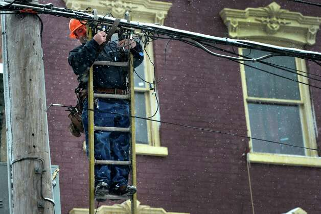 Cable guy Robert Dellaporta hooks up a customer on Lark Street during a snow storm  March 8, 2013, in Albany, N.Y.   (Skip Dickstein/Times Union) Photo: SKIP DICKSTEIN