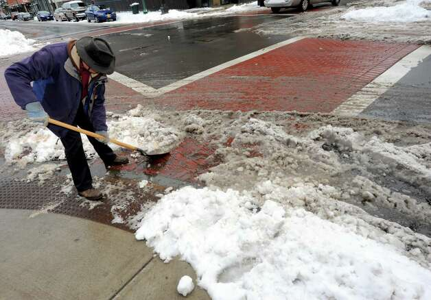 Rome Romagnoli of the Troy BID clears a crosswalk of slush at Third Street and Broadway on Friday March 8, 2013 in Troy, N.Y. (Michael P. Farrell/Times Union) Photo: Michael P. Farrell