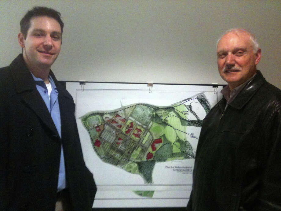 Entrepreneur Peter D'Amico, right,  and son Matt stand before a rendering of D'Amico's conceptual plan to redevelop the Fairfield Hills campus in Newtown, Conn, Thursday, March 7, 2013. It includes a stadium for semi-pro world soccer team, a children's museum, boutiques, restaurants, an office complex, a 5k walking trail, picnic areas and a memorial space to honor victims of Sandy Hook school tragedy. The plan also calls for 30 second-floor luxury apt. over businesses, and would require demolition of most of the remaining hospital buildings. Photo: Nanci Hutson / The News-Times