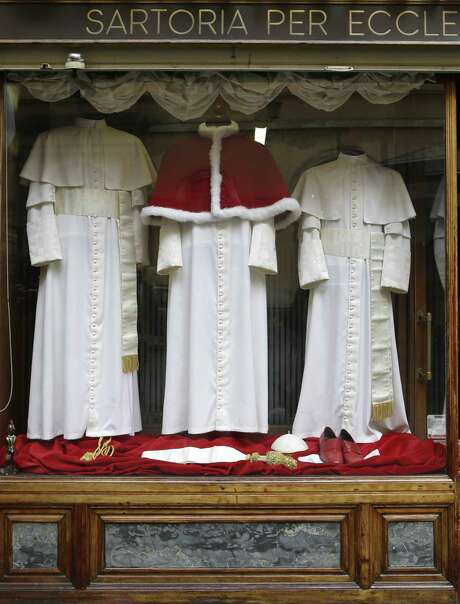 Three sets of papal outfits are displayed in the window of Gammarelli tailoring shop in Rome. Photo: Associated Press