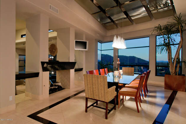 Dining area with view of the AZ hillside. Notice the TV along the left?  Don't see that too often in a formal dining area.