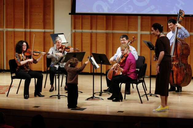 Philharmonic musicians play with a young participant at a Very Young Peopleís Concert. Musicians, left to right, are Anna Rabinova, Fiona Simon, Qiang Tu, Judith Nelson, Rebecca Young and Satoshi Okamoto. Photo: Contributed Photo