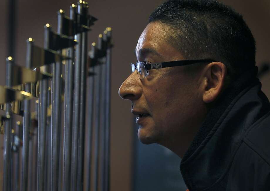 Nery Santizo checks out the San Francisco Giants' World Series trophies in San Mateo during a stop on the trophies' preseason tour around Northern California. Photo: Paul Chinn, The Chronicle