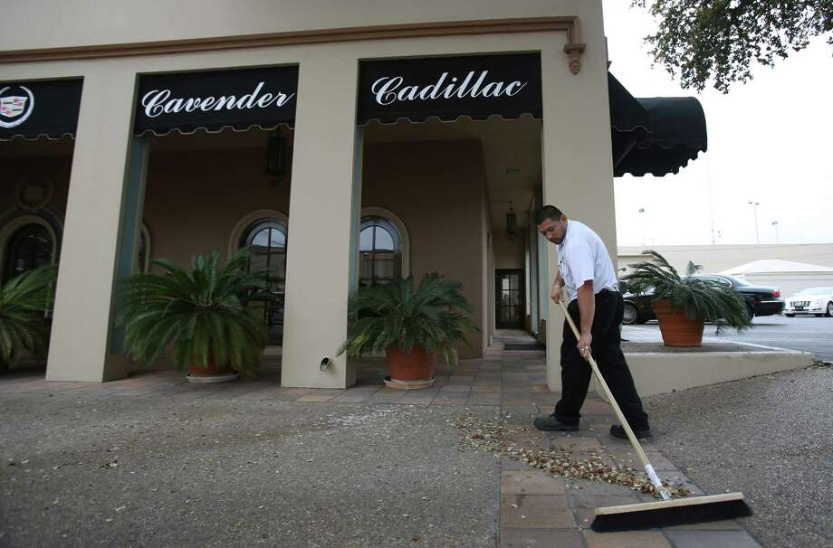 Anthony Galindo sweeps leaves outside of Cavender Cadillac, at 801 Broadway, on Friday March 8, 2013.  The location will shut down once the dealership moves to a new location at Loop 1604 and Lookout Road next summer. Photo: Helen L. Montoya, San Antonio Express-News / ©2013 San Antonio Express-News