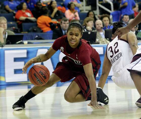South Carolina guard Sancheon White (20) slips as she drives past Texas A&M guard Adrienne Pratcher (32) during the first half of their NCAA college basketball game in the Southeastern Conference tournament, Friday, March 8, 2013, in Duluth, Ga. (AP Photo/John Bazemore) Photo: John Bazemore, Associated Press / AP