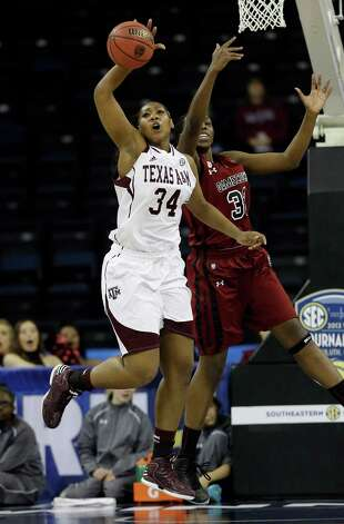 Texas A&M center Karla Gilbert (34) intercepts a pass in front of South Carolina forward Elem Ibiam (33) during the second  half of their NCAA college basketball game in the Southeastern Conference tournament on Friday, March 8, 2013, in Duluth, Ga. Texas A&M won 61-52.  (AP Photo/John Bazemore) Photo: John Bazemore, Associated Press / AP