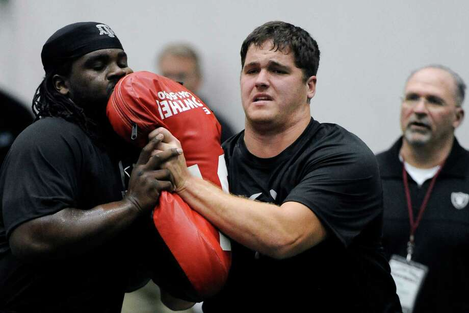 Texas A&M's Luke Joeckel, right, works a drill for NFL scouts Friday, March 8, 2013 in College Station, Texas. Joeckel may be the top overall pick in April's NFL draft. (AP Photo/Pat Sullivan) Photo: Pat Sullivan, Associated Press / AP