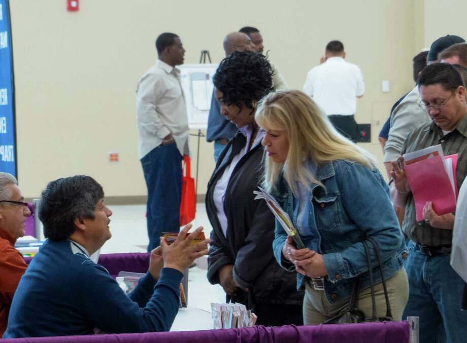 Lana Davenport, who is looking for an outside position in warehousing and parts assistance, speaks with Jose Alberto Morales of Hill Country Well Service during the Oil & Gas Industry Job Fair in Floresville, Texas, on Tuesday, March 5, 2013. Photo: Billy Calzada, San Antonio Express-News / San Antonio Express-News