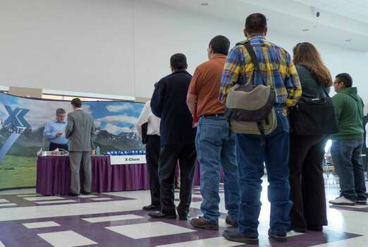People line up for a chance to speak with an X-Chem representative during the Oil & Gas Industry Job Fair in Floresville, Texas, on Tuesday, March 5, 2013. Photo: Billy Calzada, San Antonio Express-News / San Antonio Express-News