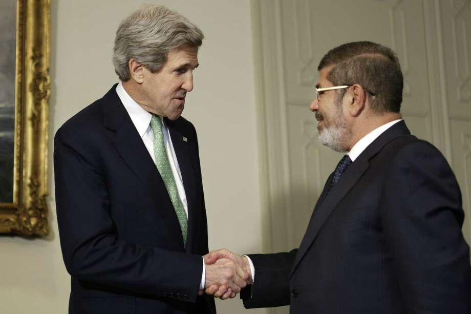 U.S. Secretary of State John Kerry (left) presented Egyptian President Mohamed Morsi with $250 million in foreign aid. Photo: Jacquelyn Martin / Associated Press