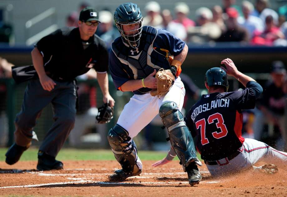 Joey Terdoslavich slides past Astros catcher Chris Wallace to score a run during the first inning. Photo: Evan Vucci