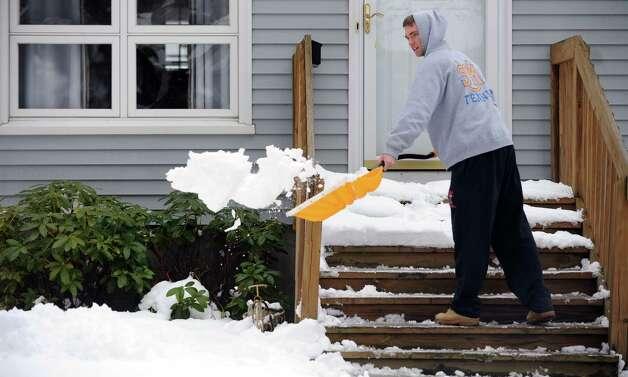 Craig Spann clears his front steps in Fairfield, Conn. Friday, Mar. 8, 2013 as snow falls across the region. Photo: Autumn Driscoll