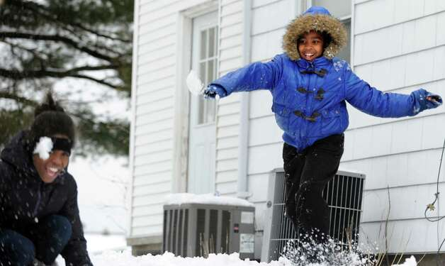 Tiombe Brown, 10, sends a snowball sailing toward Janelle Johnson, 11, as they enjoy the snow day in Bridgeport, Conn. Friday, Mar. 8, 2013. Photo: Autumn Driscoll