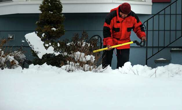 Noberto Mani shovels a walkway in Fairfield, Conn. Friday, Mar. 8, 2013 as snow falls across the region. Photo: Autumn Driscoll