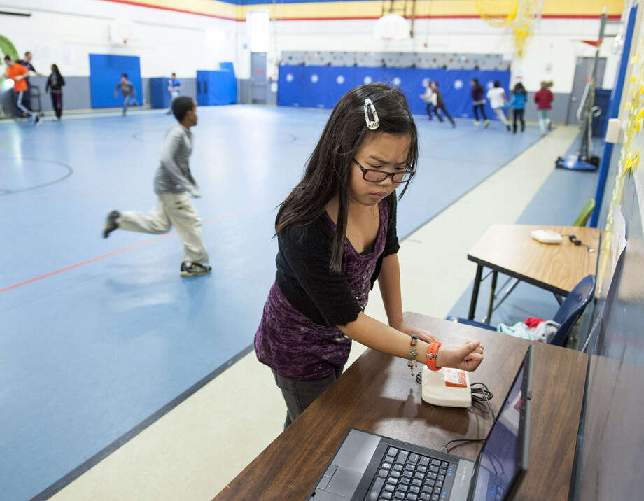 My Chi, an 11-year-old at Patrick Henry Elementary in Virginia, gets credit for her exercises with her Sqord accelerometer, which records kids' activities and encourages exercise. Photo: Katherine Frey / The Washington Post