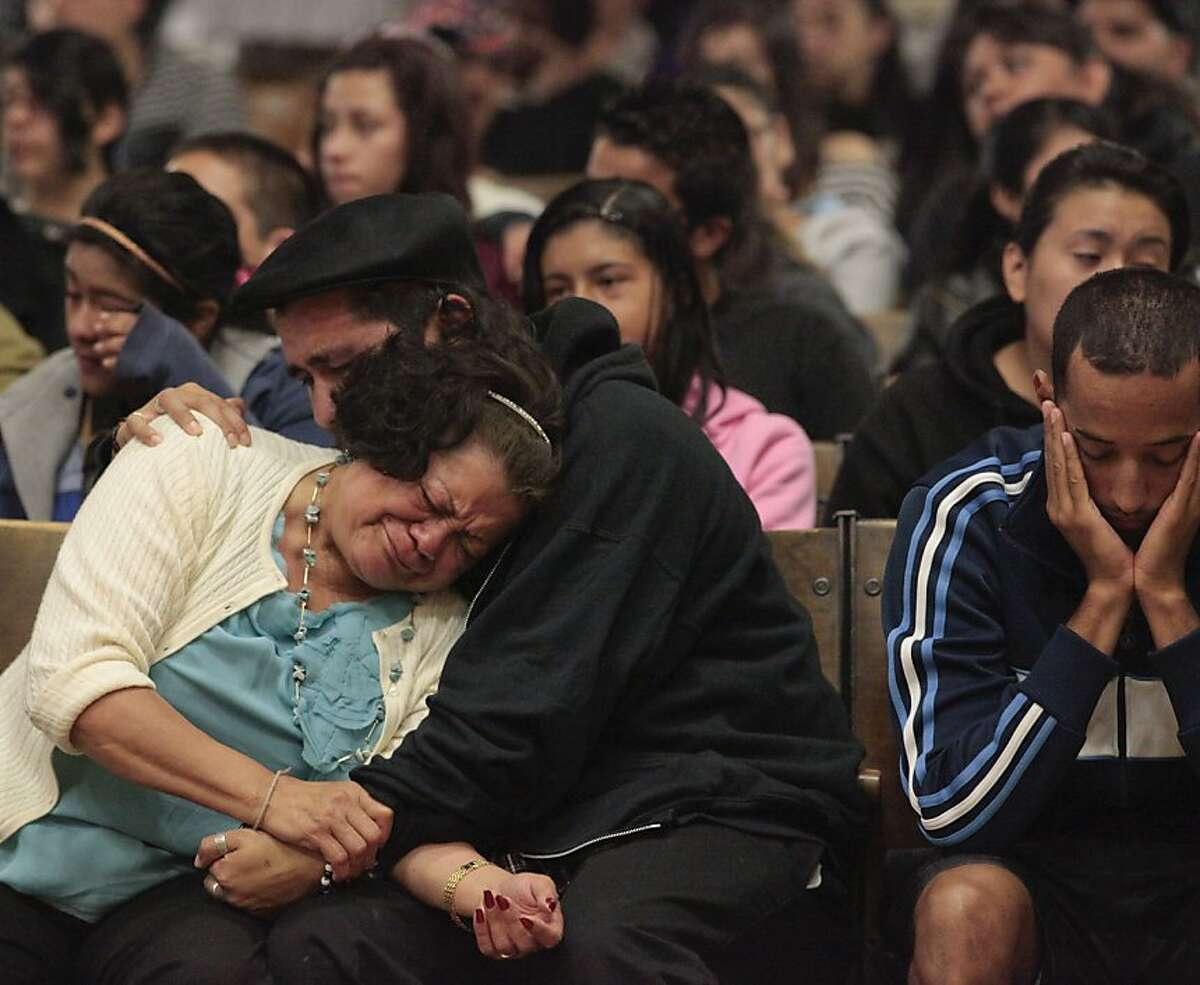 Oakland Unified School District employee Emma Paulino, left is comforted teacher Julio Magna during a memorial service for student Alejandro Aguilera, Monday June 4, 2012, at the Life Academy High School in Oakland, Calif. The school faculty held an assembly to help the students with the loss of their classmate Alejandro Aguilera, who was killed the Friday before in a drive-by shooting.