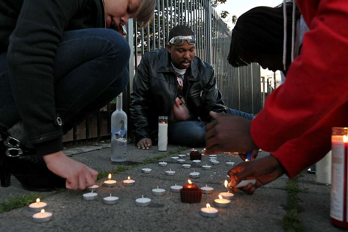 Brijjanna Price, left, joins her father Ramon and friends as they  light candles to mark the one year anniversary of the killing of her brother Lamont, Saturday February 16, 2013, in Oakland, Calif. Lamont Price, 17, was killed in the 8100 block of Birch Street in broad daylight. Photo: Lacy Atkins, The Chronicle