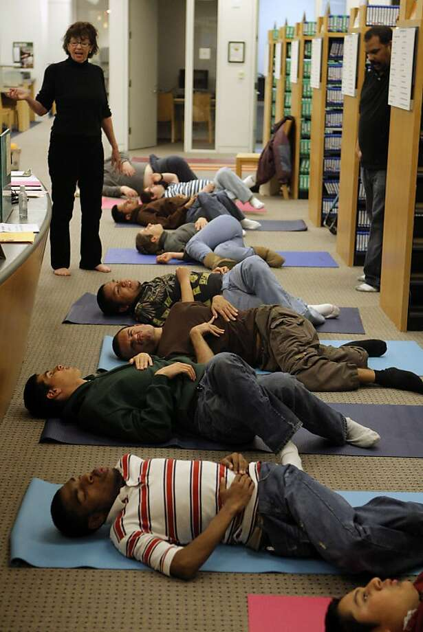 Nancy Yates (left) leads a yoga class for the visually impaired at the main library. Photo: Jessica Olthof, The Chronicle