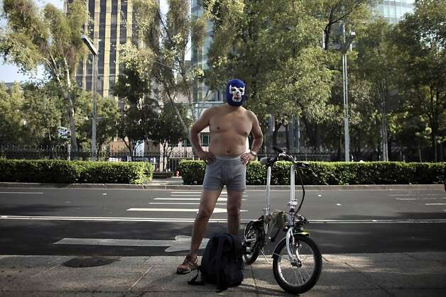 A cyclist wearing a lucha libre wrestling mask, underwear and shoes stands by his bike before participating in The World Naked Bike Ride to demand respect from motorists and protest the car-oriented culture in Mexico City, Saturday June 11, 2011.