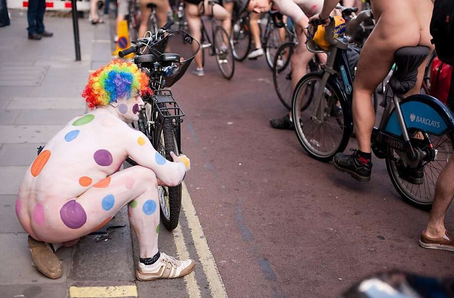 A man repairs a puncture as he takes part in the annual London World Naked Bike Ride event in central London on June 11, 2011. Now in it's tenth year, the event has seen participation grow from 58 in 2004 to 1,200 in 2009. Taking a route that passes many of London's most famous landmarks, the ride allows those participating to decorate their body with messages of protest against oil dependancy and motor vehicle usage. AFP PHOTO